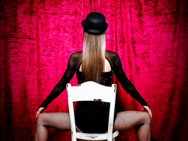Female sat on chair in Fosse style