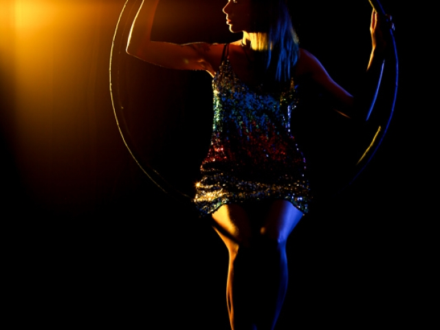 Aerial Hoop in a yellow spotlight with sparkly dress