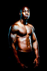 Male muscles with tattoos and dramatic lighting