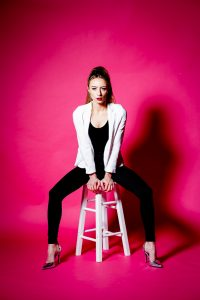 Model sat on stool in a white jacket and black jeans with pink paper background